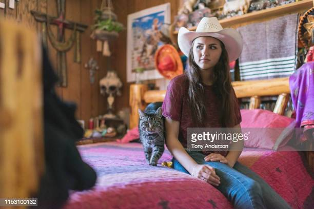 teenage girl in cowboy hat in her bedroom - cat with red hat stock pictures, royalty-free photos & images
