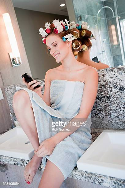 Teenage girl in curlers text messaging