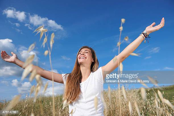 Teenage girl in field with arms out, Tuscany, Italy