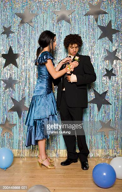 Teenage girl (16-18) in formal dress adjusting young man's boutonniere