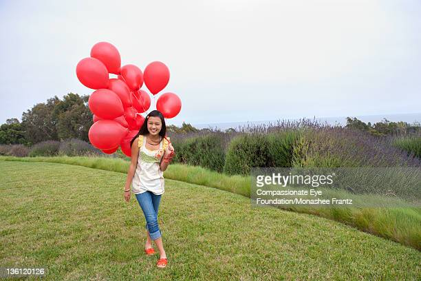 teenage girl in garden, holding bunch of balloons - compassionate eye foundation stock pictures, royalty-free photos & images