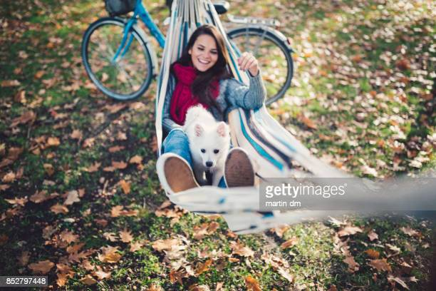 Teenage girl in hammock playing with her dog