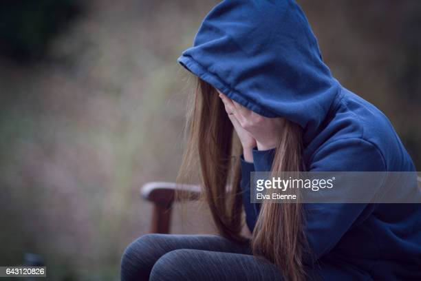 Teenage girl in hooded top, with head in hands in despair