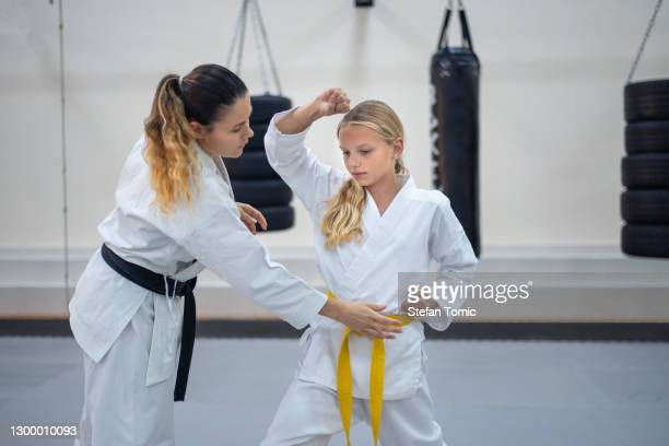 teenage girl in kimono practicing karate with a instructor in a sports gym. martial arts training session - martial arts stock pictures, royalty-free photos & images