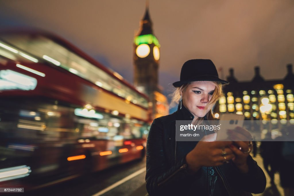 Teenage girl in London texting by night : Stock Photo