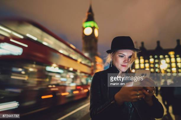 Teenage girl in London texting by night