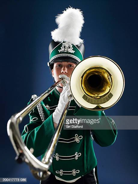 Teenage girl (15-17) in marching band uniform playing trombone