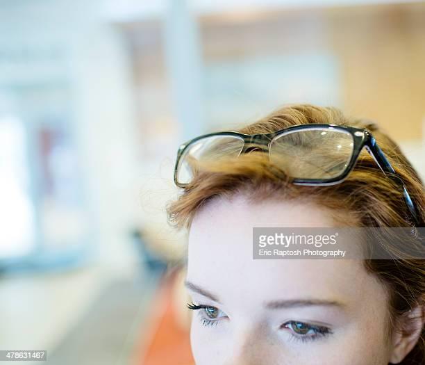 Teenage girl in office wearing glasses on head