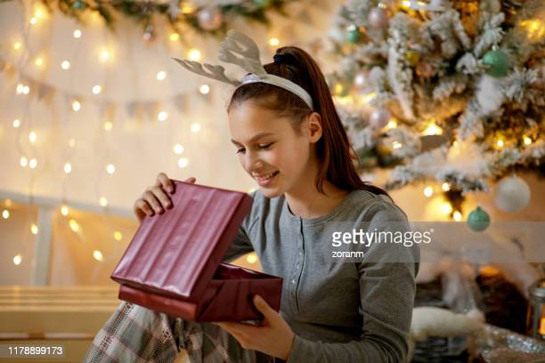 teenage girl in pajamas and antler headband opening christmas gift - teenagers only stock pictures, royalty-free photos & images