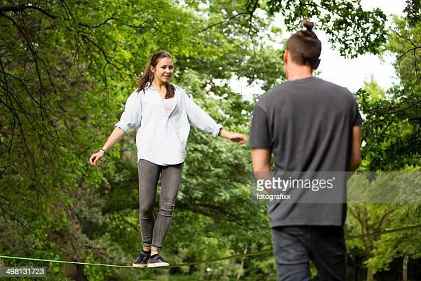 teenage girl in park balancing on a slack line