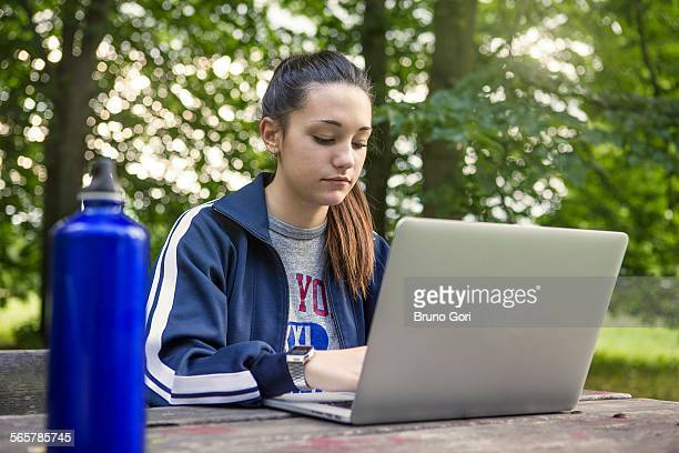 Teenage girl in park using laptop at picnic bench