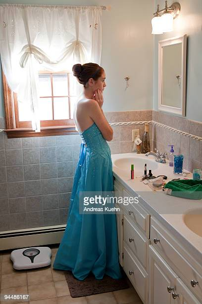 Teenage girl in prom dress looking in mirror.