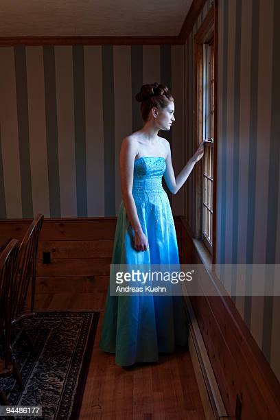 Teenage girl in prom dress looking out of window.
