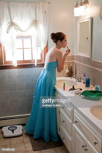 Teenage girl in prom dress putting on lipstick.