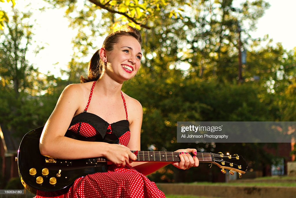 teenage girl in red dress plays guitar stock photo getty images