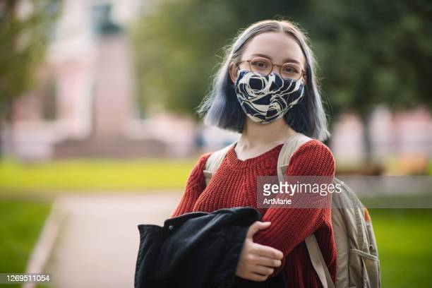 teenage girl in reusable protective face mask outdoors in campus or schoolyard. new normal and back to school concept after covid-19 quarantine - campus stock pictures, royalty-free photos & images
