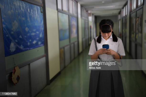 teenage girl in school uniforms using smartphone - online bullying stock pictures, royalty-free photos & images