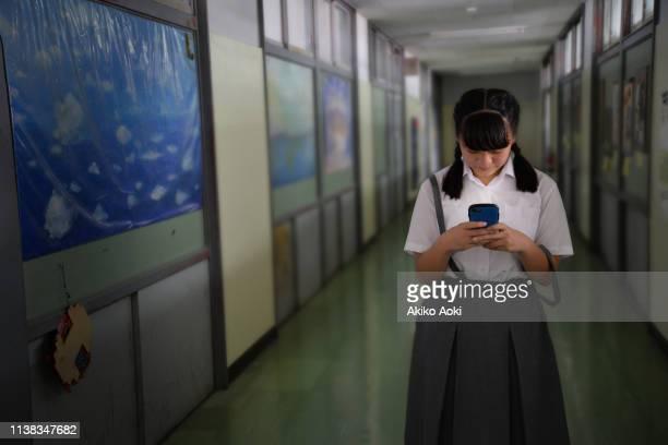 teenage girl in school uniforms using smartphone - cyberbullismo foto e immagini stock