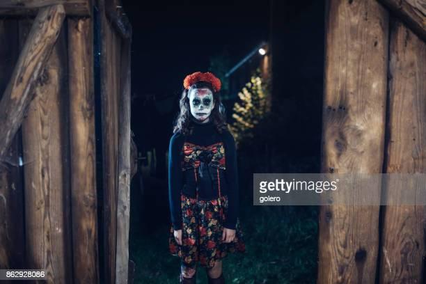teenage girl in spooky halloween costume in front of old barn