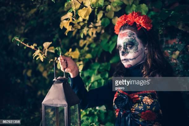 teenage girl in spooky halloween costumes with lantern