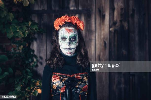 teenage girl in spooky halloween mask in front of old barn