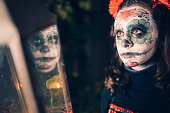 teenage girl in spooky halloween mask with lantern