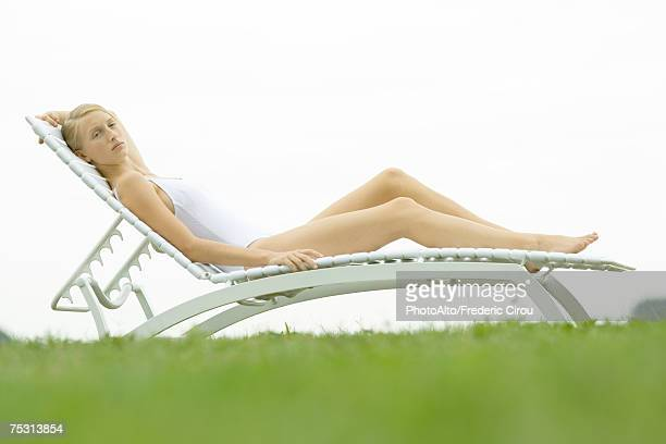 Teenage girl in swimsuit sitting on lounge chair