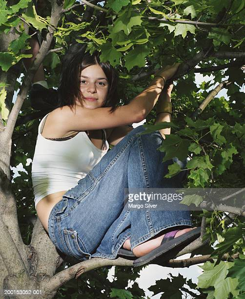 teenage girl (14-16) in tree smiling, portrait - girl wear jeans and flip flops stock photos and pictures
