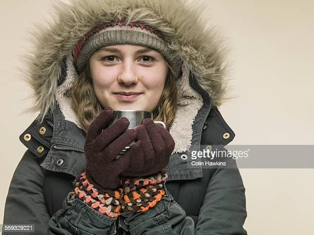 teenage girl in warm clothes holding cup - colin hawkins stock pictures, royalty-free photos & images