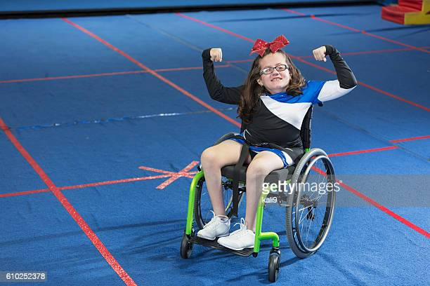 Teenage girl in wheelchair wearing cheerleading uniform