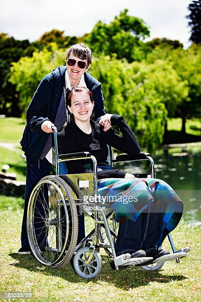 Teenage girl in wheelchair with elderly carer hold hands, smile