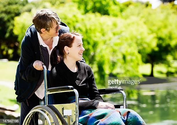 Teenager-Mädchen im Rollstuhl mit älteren Pflegekraft Lächeln von lake