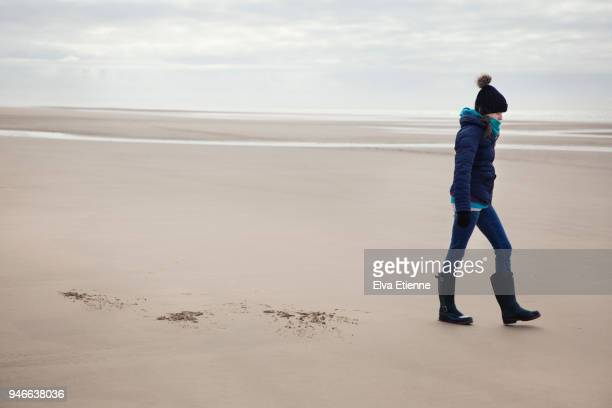 Teenage girl in winter clothing walking along a deserted sandy beach