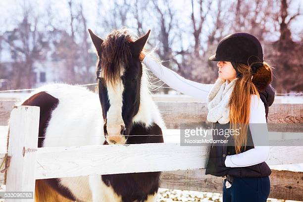 Teenage girl in winter riding gear stroking a pony