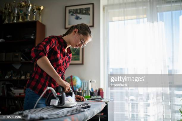 teenage girl ironing clothes at home - chores stock pictures, royalty-free photos & images