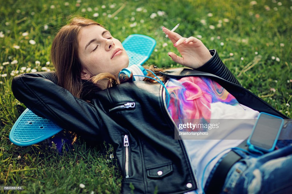 Teenage girl is lying down and smoking cigarette : Stock Photo