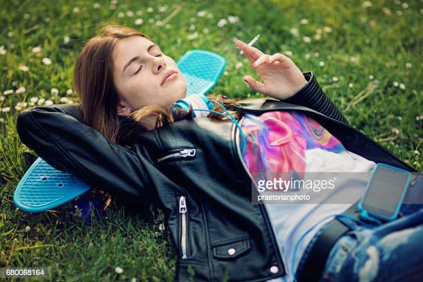 teenage girl is lying down and smoking cigarette - little girl smoking cigarette stock photos and pictures