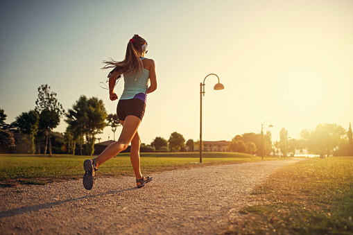 Teenage girl jogging in city park 1061745418