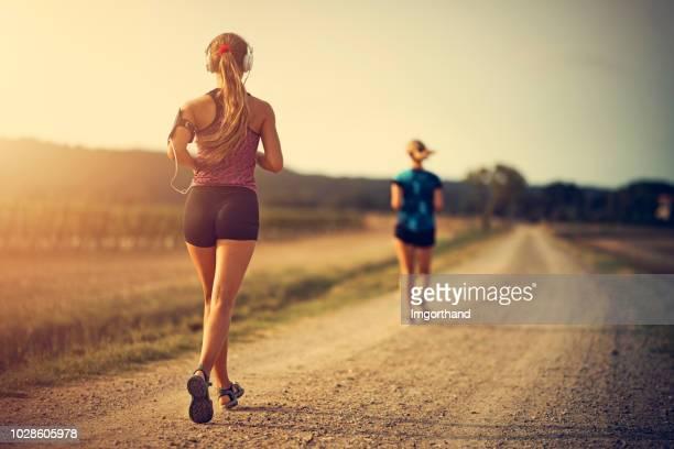 10 代の少女が田舎道で母とジョギング
