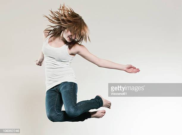 Teenage girl (16-17) jumping against gray background