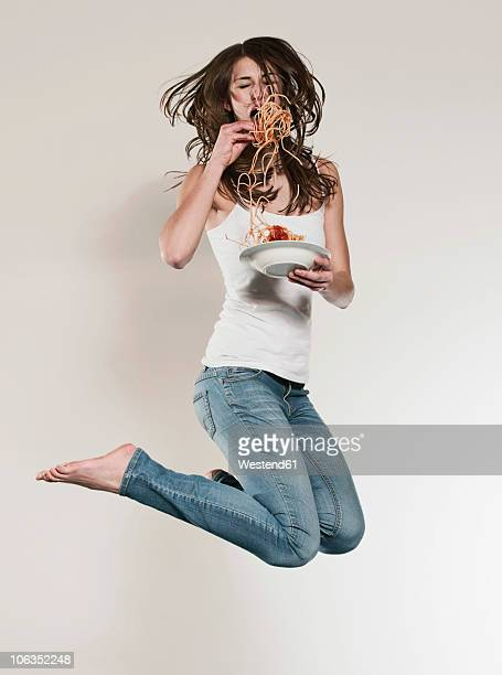 Teenage girl (16-17) jumping and eating noodles