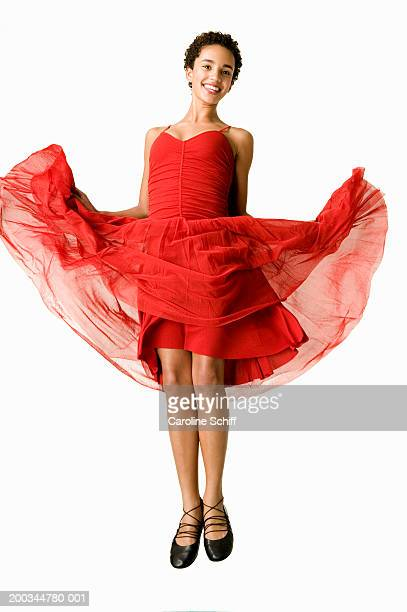 teenage girl (14-16) jumping and lifting dress, smiling, portrait - schiff stock photos and pictures