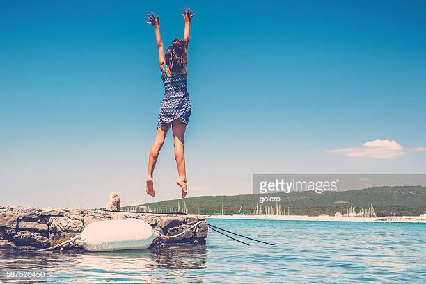 teenage girl jumping high at croatian coast