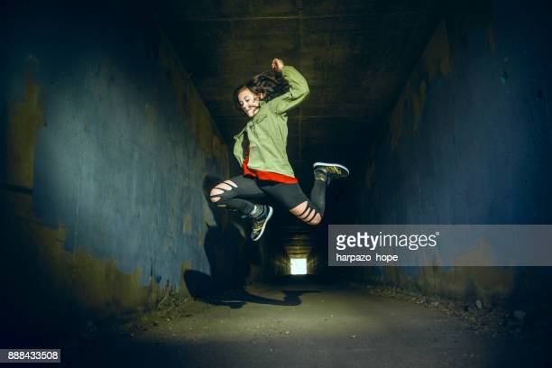 teenage girl jumping in a tunnel - opstand stockfoto's en -beelden