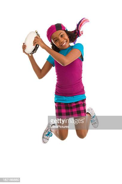 Teenage girl jumping in air holding tambourine