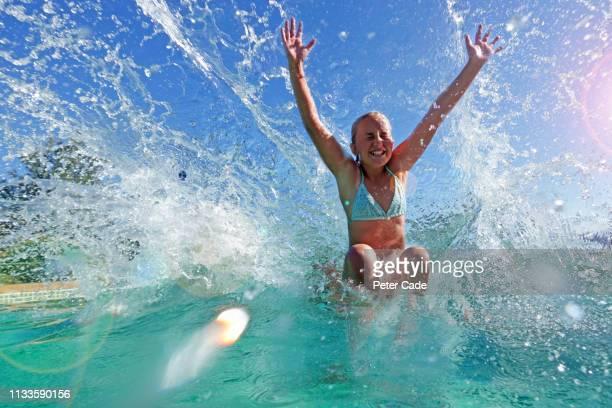 teenage girl jumping in pool - piscina pubblica all'aperto foto e immagini stock