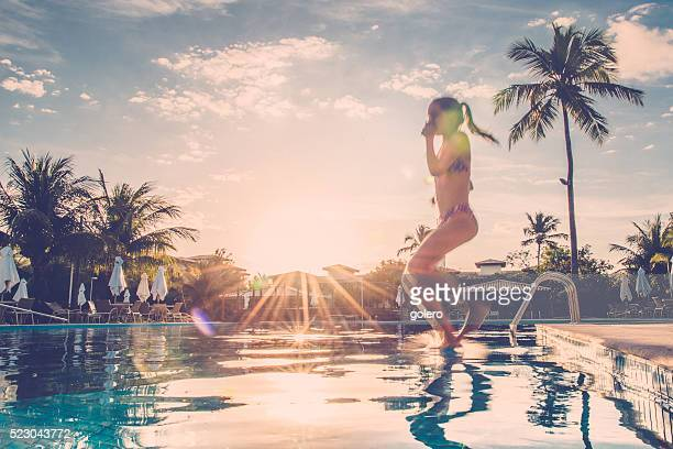 teenage girl jumping into swimming pool at sundown