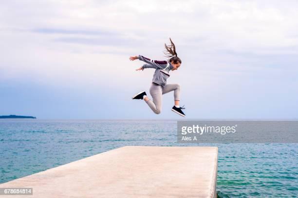 桟橋の端にジャンプ十代の少女