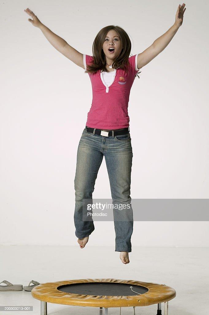 Teenage girl (16-17) jumping on trampoline in studio : Stock Photo