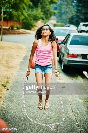 Teenage girl jumping rope on neighborhood sidewalk